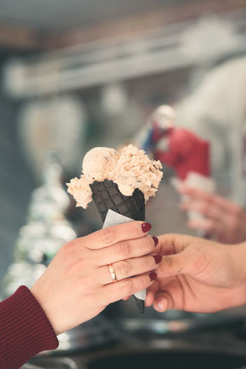 Woman buying couple scoops of ice cream in a candy shop by street. woman putting scoops of icecream