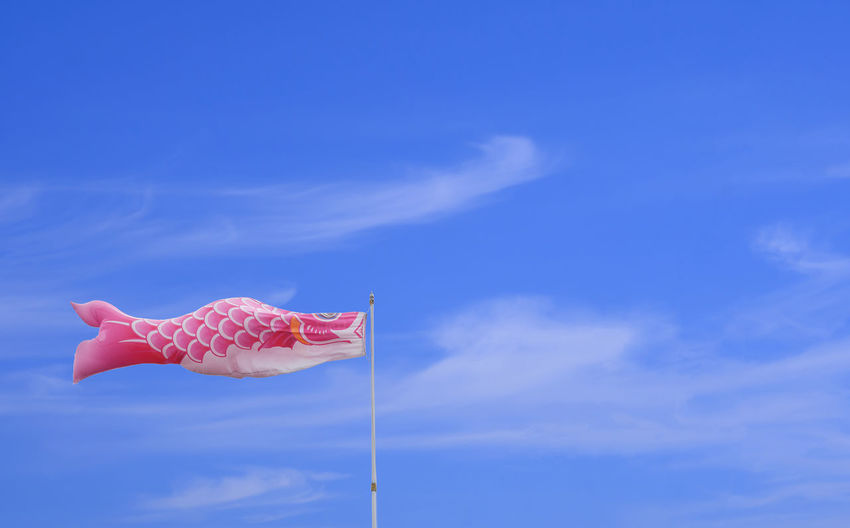 Low angle view of pink flag against blue sky