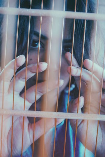Close-up portrait of woman seen through window