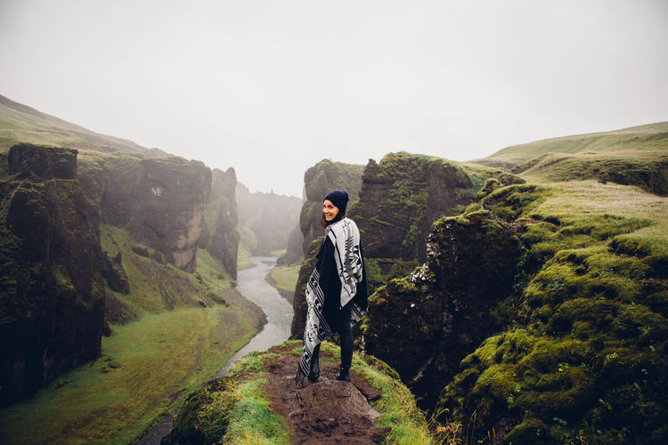 Young man on cliff against mountains
