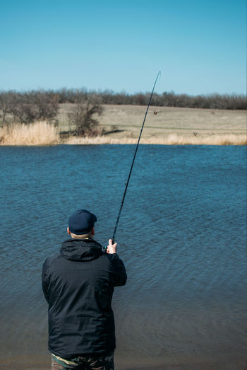 Rear view of man fishing in water