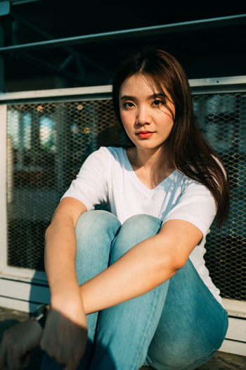 Portrait of a beautiful young woman sitting on railing