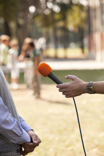 Close-up of hand holding microphone against man