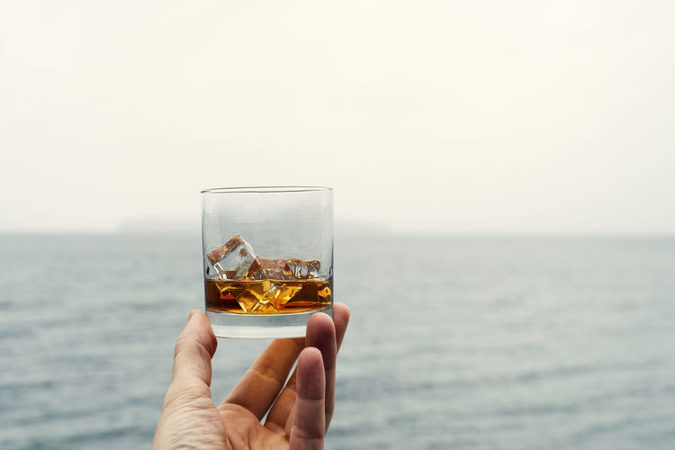 Premium alcohol on ice in hand over misty rainy day sea.
