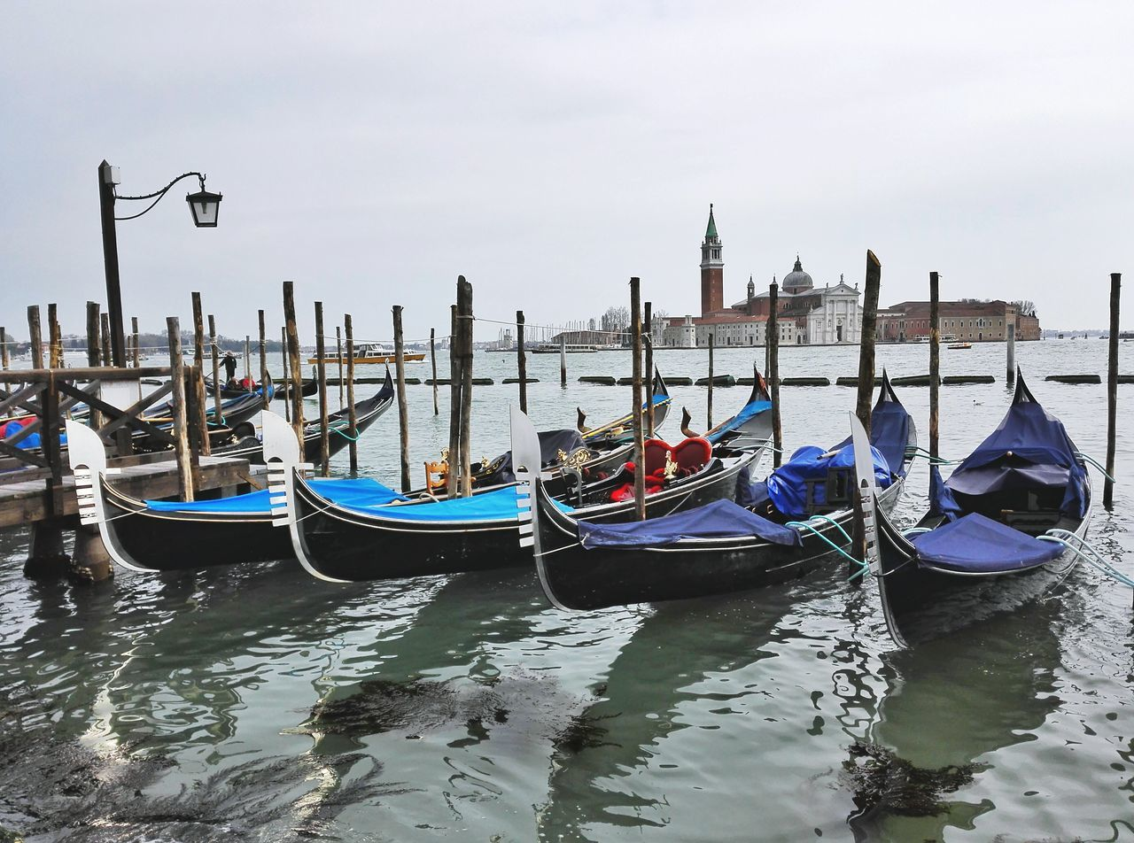 moored, gondola - traditional boat, water, travel destinations, waterfront, no people, transportation, reflection, nautical vessel, day, gondola, outdoors, architecture, built structure, building exterior, sky, nature