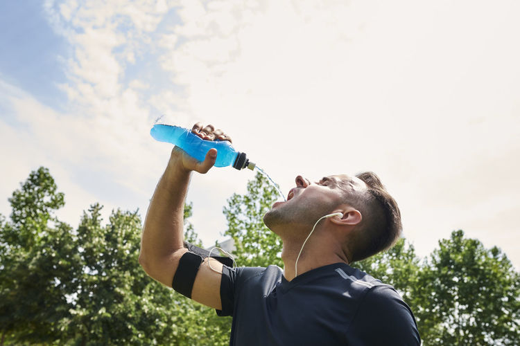 Young man drinking drink in bottle against sky