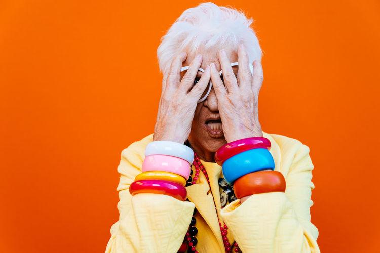 Portrait of tensed senior woman wearing eyeglasses against red background