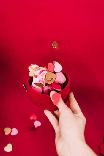 Close-up of woman hand holding pink petals against red background