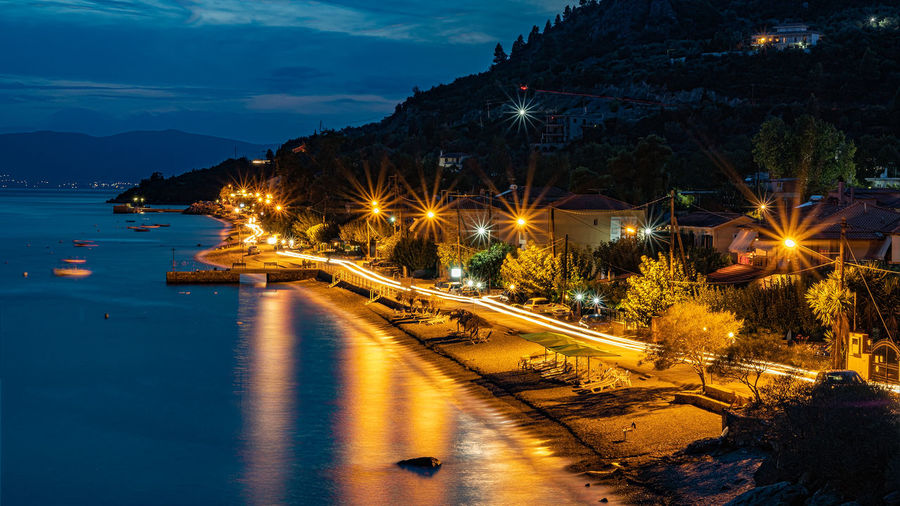 Illuminated city by street against sky at night
