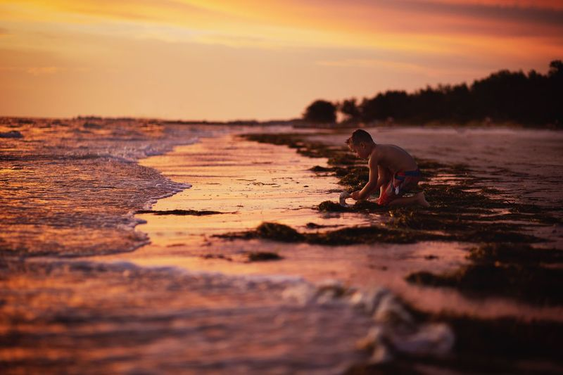 Boy playing at shore of beach during sunset