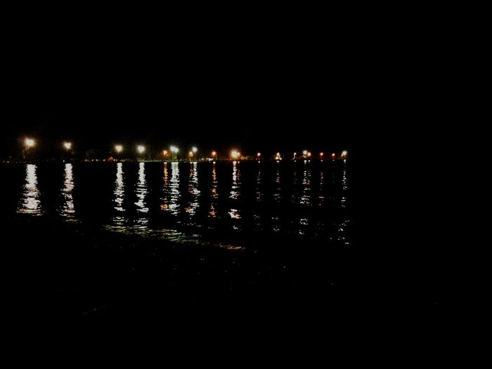 Night Water Reflection Street Light Dark Sea Outdoors Electric Light Ocean Scenics No People Urbanscape Black And Colors In A Row Long By The Sea Majestic Waterfront Calm Beauty In Nature Beach Beachview