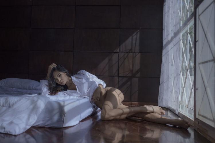 Full length portrait of semi-dress woman lying on floor at home