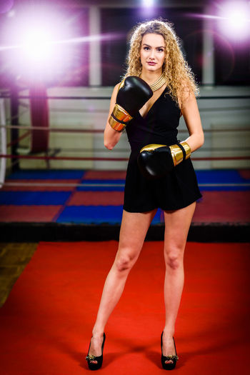 Portrait Of Beautiful Woman Wearing Boxing Gloves Against Ring
