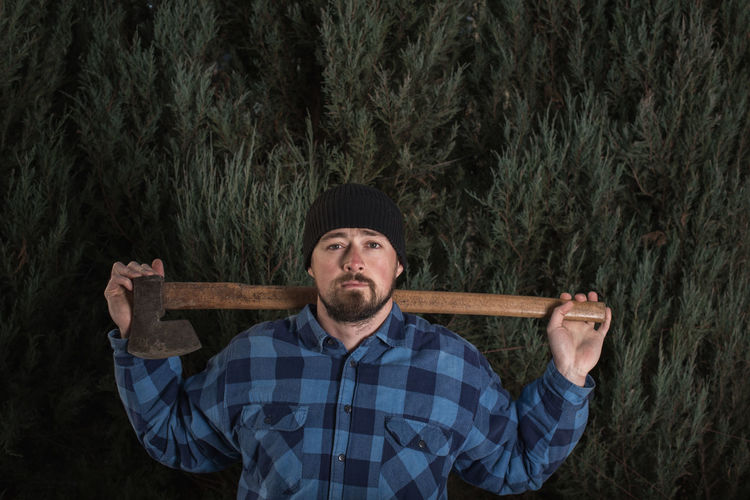 Portrait of lumberjack holding axe while standing against trees at forest