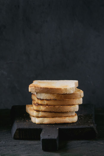 Stack of Fresh toasts bread on black wooden cutting board over black textured background. Breakfast Toast Baked Black Background Bread Breakfast Cutting Board Food Food And Drink Ready-to-eat Stack Table Toasted Bread Unhealthy Eating White Bread
