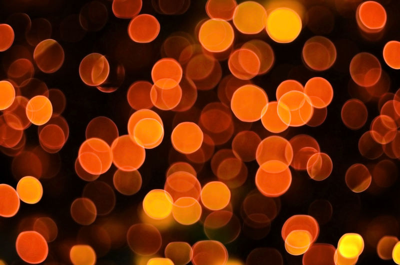 Defocused image of illuminated lights against black background