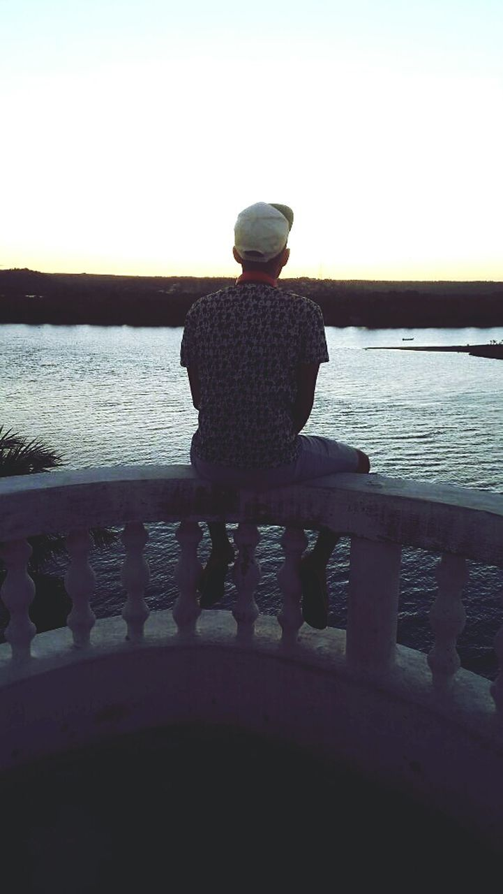 sea, rear view, water, railing, one person, nature, silhouette, tranquility, outdoors, beauty in nature, scenics, standing, men, day, real people, horizon over water, full length, sunset, sky, one man only, adult, people