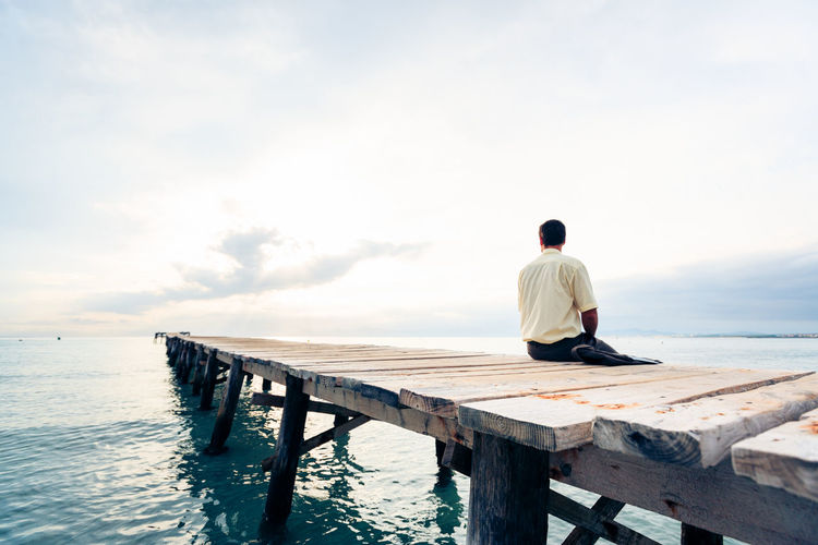 Businessman sitting on jetty over sea against sky