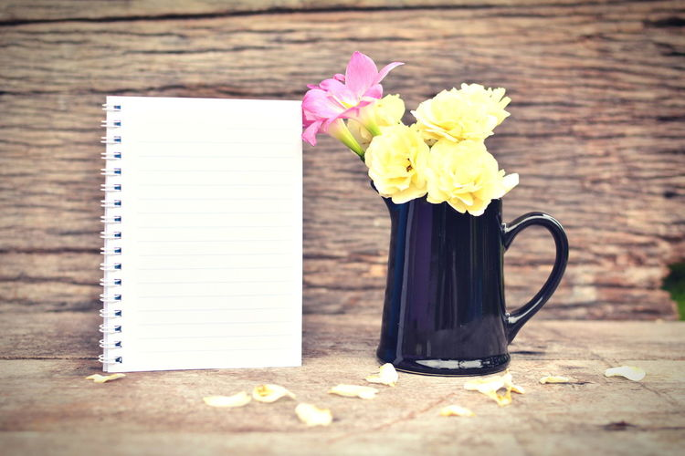 Yellow and pink flowers in pitcher with spiral notebook on wooden table