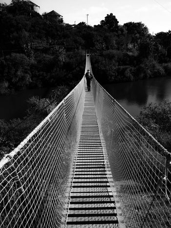 Tree Bridge - Man Made Structure Connection Outdoors The Way Forward Day Suspension Bridge Architecture Sky Father & Son Fatherhood Moments FatherSonMoments Fatherandsonmoments Blackandwhite Courage Manthing Bridge Bridge View Fearless