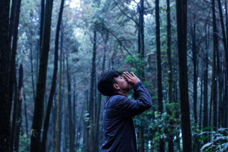 Side view of young man in forest