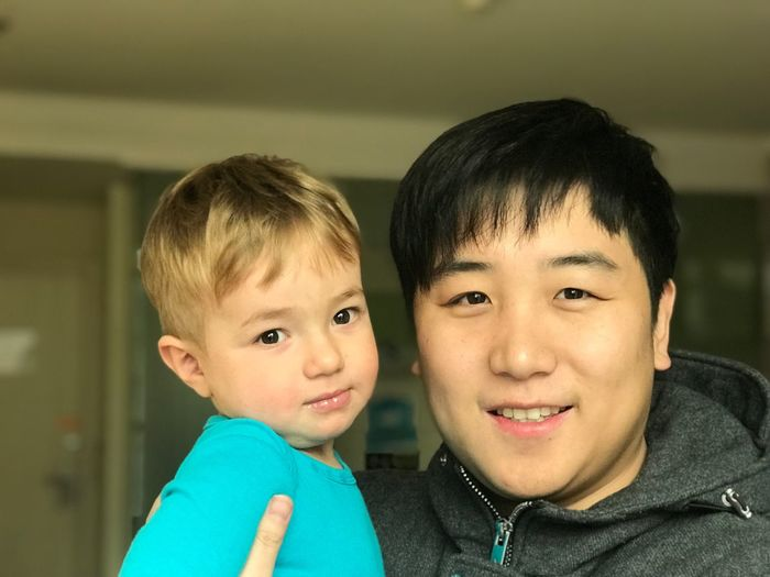 Portrait of smiling man and boy at home