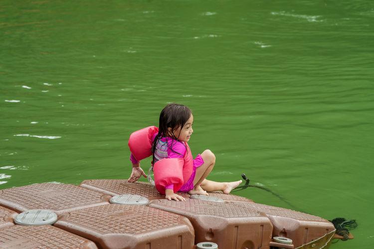 Full length of girl on pontoon bridge in lake