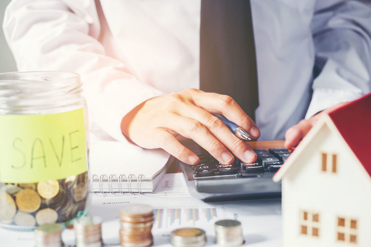 Midsection Of Businessman Using Calculator By Jars With Coin And Model Home