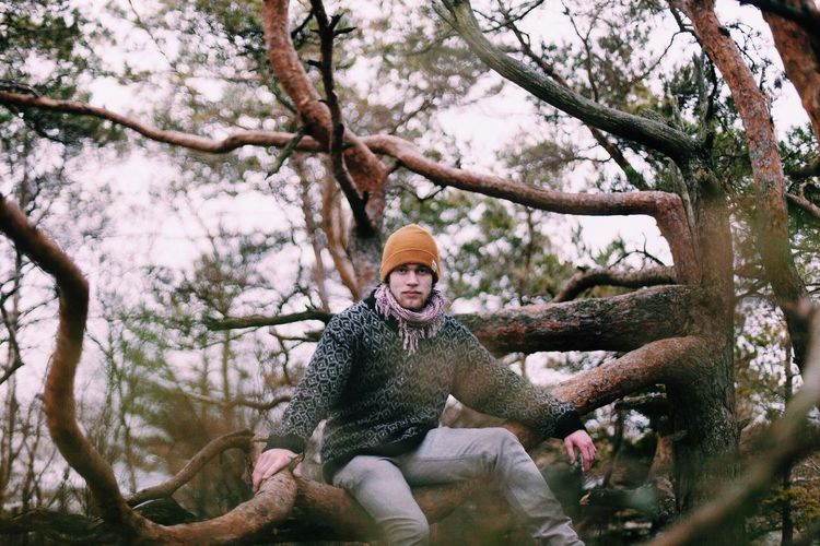 Portrait of young man standing on tree trunk