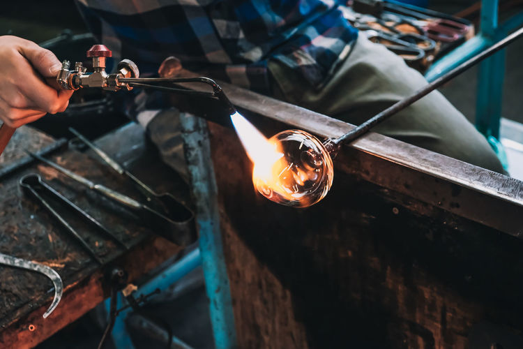Glassblowing a whisky tumbler Small Business Blacksmith  Close-up Craftsperson Day Factory Fire Flame Glass Blowing Heat - Temperature Human Body Part Human Hand Indoors  Industry Making Metal Occupation One Person People Real People Skill  Tourch Work Tool Working Workshop Business Stories