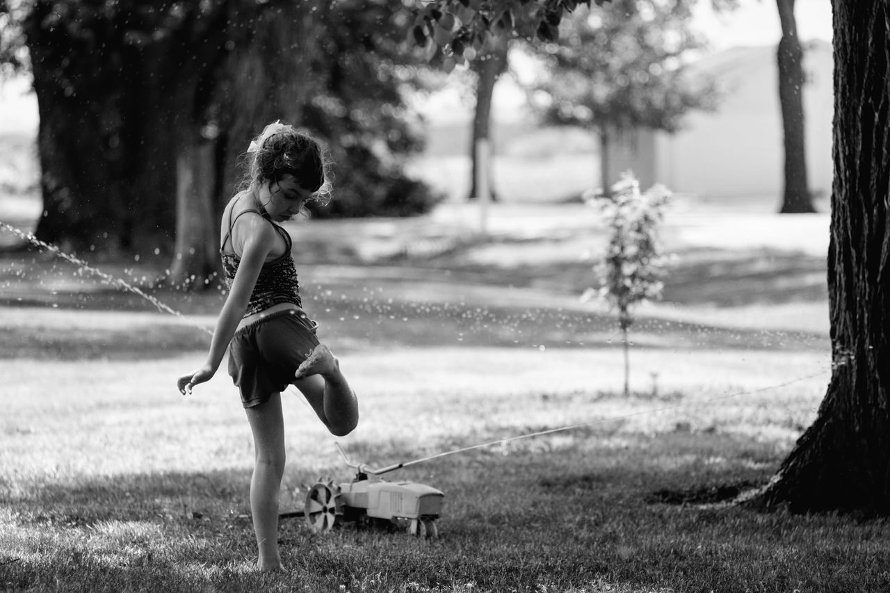 Girl Playing With Sprinkler Water At Park