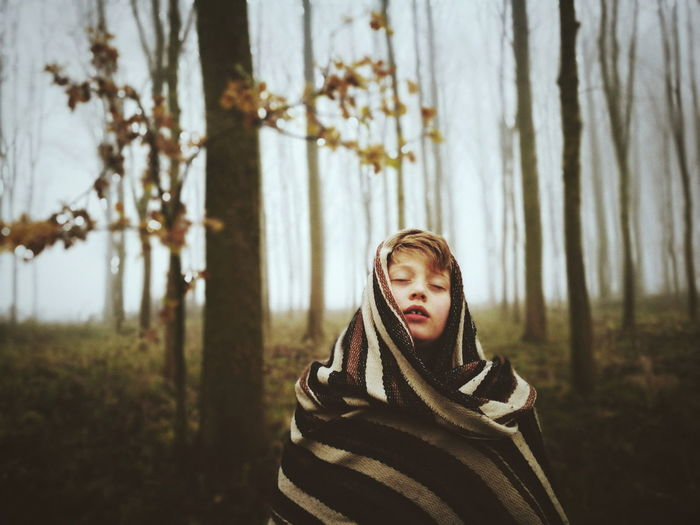 Boy with eyes closed wrapped in blanket at forest during winter
