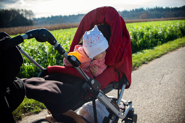 Cute toddler girl in baby carriage on roadside