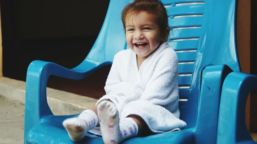 Cute smiling girl wrapped in towel sitting on blue chair