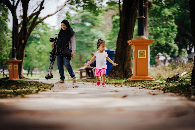 Rear view of women walking on footpath