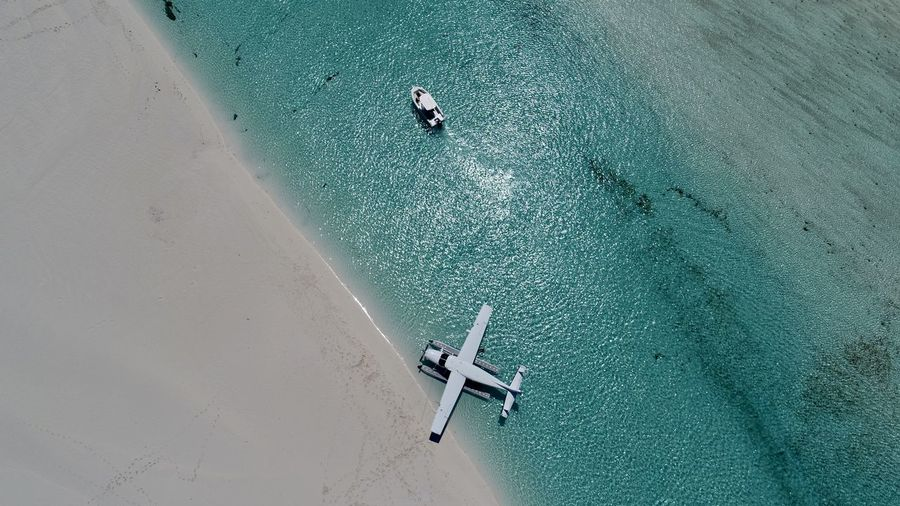 Aerial view of seaplane and boat in sea