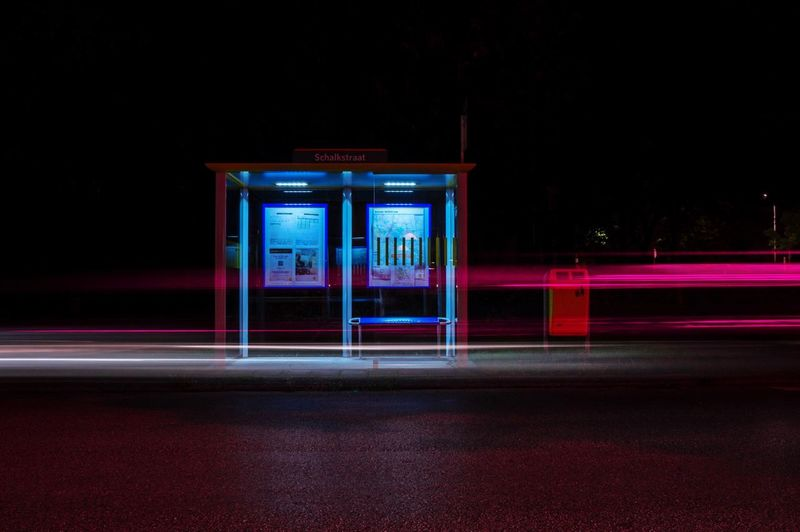 Light trails on road against bus stop at night