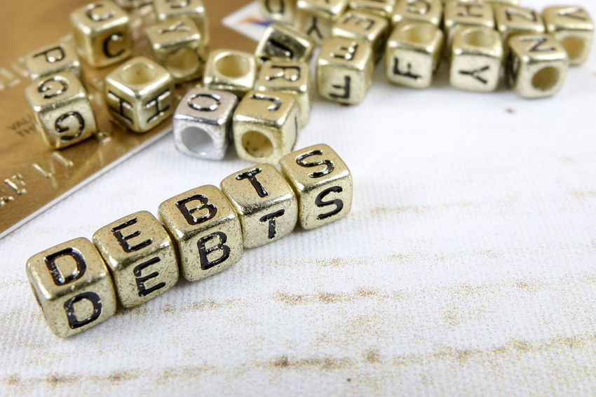 DEBT CONCEPT WITH GOLD DICE ON A WOODEN TABLE Alphabet Capital Letter Close-up Communication Credit Card Debt Crisis Group Of Objects High Angle View Indoors  Large Group Of Objects Leisure Activity Leisure Games Letter No People Number Still Life Studio Shot Table Text Toy Toy Block Western Script