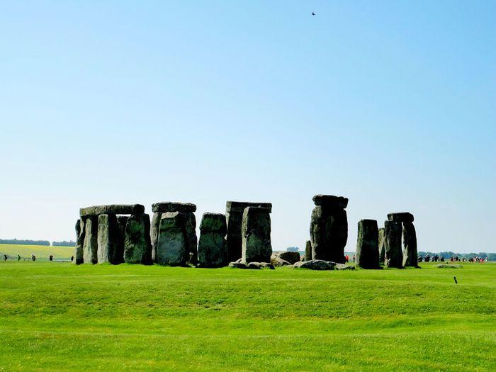 Historic stonehenge on grass against blue sky