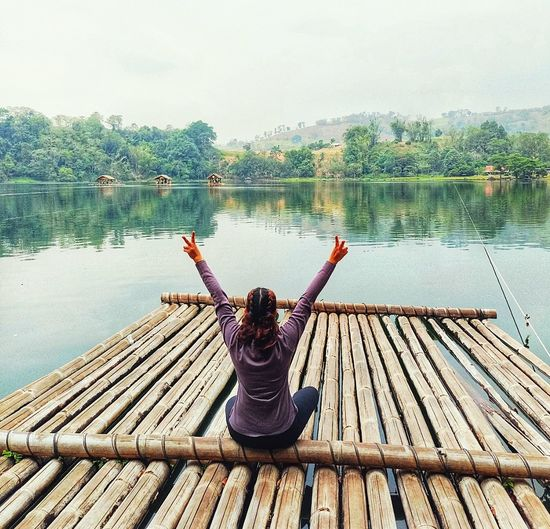Woman gesturing peace sign while sitting on wooden raft in lake