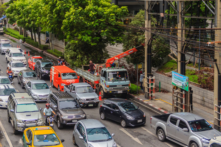 Bangkok, Thailand - April 1, 2017: Truck loader crane is lifting big roadside tree causing traffic jammed in the rush hour. Traffic Jam Traffic Jam In Bangkok Traffic Jam. Patience Architecture Building Exterior Built Structure Car City Day High Angle View Incidental People Land Vehicle Mode Of Transportation Motor Vehicle Outdoors Plant Road Street Traffic Traffic Jam Traffic Jam City Traffic Jams Transportation Tree Truck Truck Crane