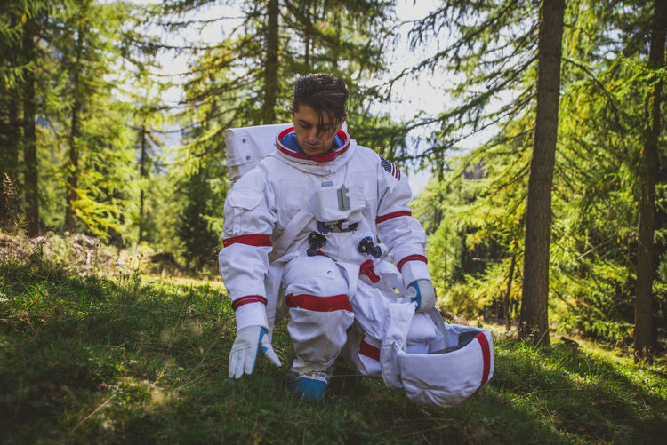 Curious astronaut crouching in forest