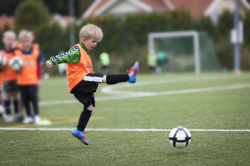 Boy playing soccer ball on grass