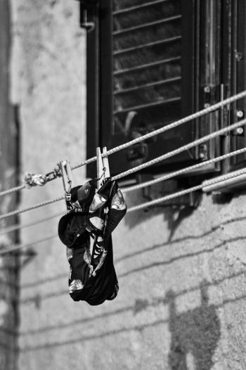 Clothes hanging on rope against wall