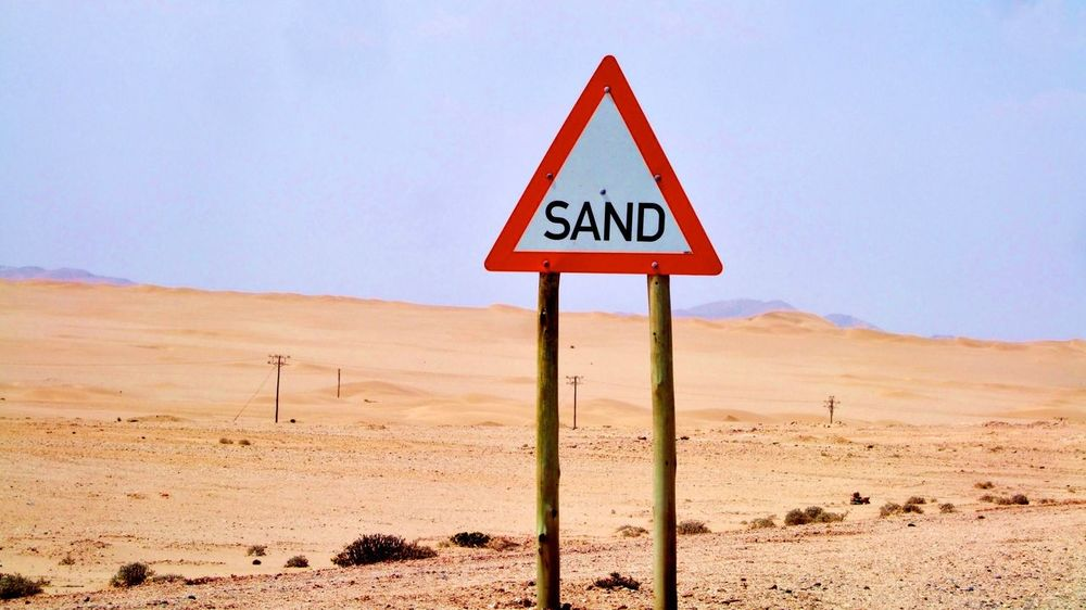Attention: Sand! Sand Desert Communication Warning Sign Arid Climate Landscape Day Danger Outdoors No People Tranquility Nature Sky Road Sign Signs Funny Unnecessary Warning