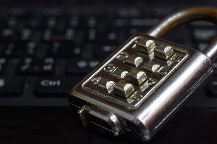 Old Password Key Lock placed on the black notebook keyboard in concept of password security in computer systems. Business Office Security Concept Cyber Data Encryption Equipment Hacker Information Internet Keyboard Computer Laptop Lock Old Key Padlock Password Privacy Protection Safety Secret Secure System Technology Virus Attack