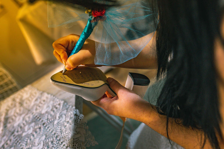 Midsection of woman writing on sandal sole