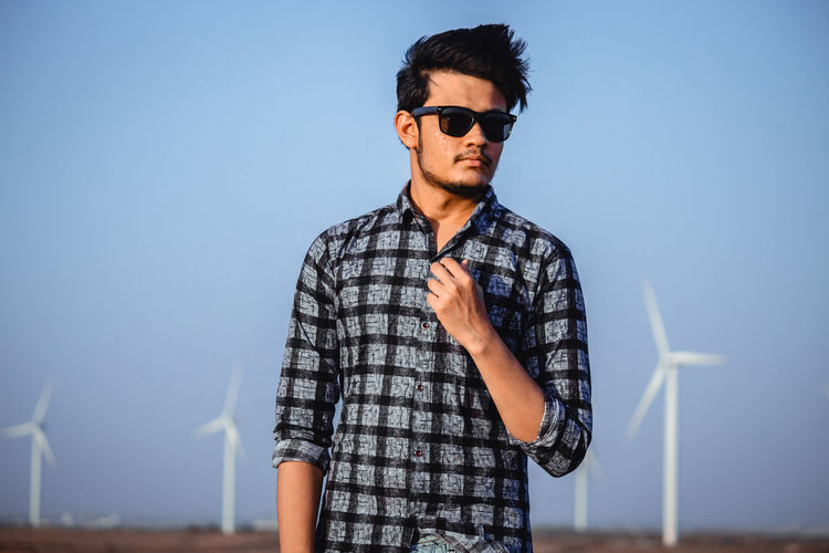 Glasses Young Adult Sunglasses Young Men One Person Renewable Energy Sky Environmental Conservation Wind Turbine Fashion Turbine Alternative Energy Fuel And Power Generation Standing Clear Sky Waist Up Casual Clothing Environment Blue Real People