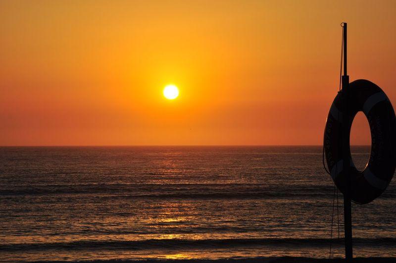 Silhouette Lifebelt On Pole At Praia Da Costa Nova Against Sky During Sunset