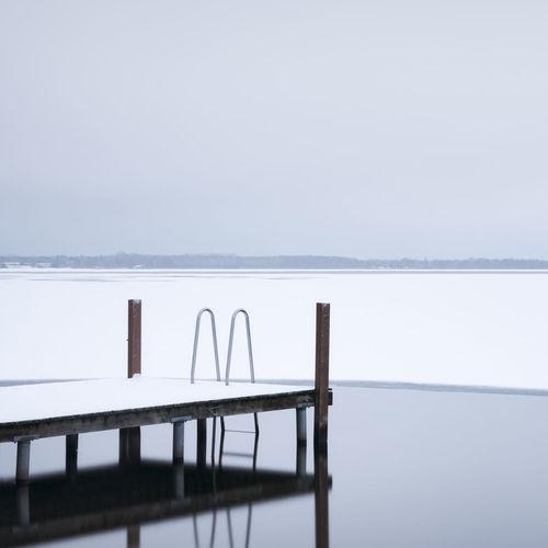 Pier by frozen lake against sky